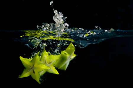 A trio of star fruit pieces create a splash as they hit the water Stock Photo - 8729365