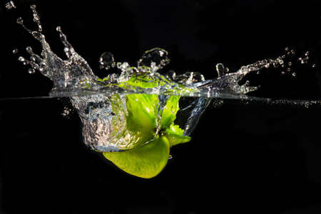 fruit in water: A falling star fruit plunges into the water creating a large splash