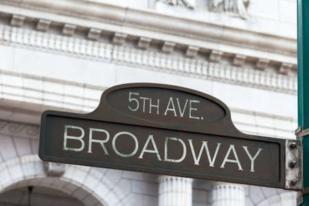 street name sign: A corroding bronze street sign indicating 5th avenue and Broadway intersection