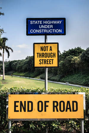 implications: Signage indicating the end of the road and implications of road expansions into the jungle