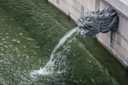 spigot: An outdoor, ornamental dragon head water spout spraying a stream of water into the pond Stock Photo