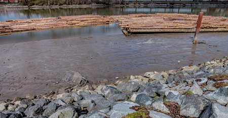 Low tide reveals the pollution under the timber, below river's surface. Stock Photo - 58302742