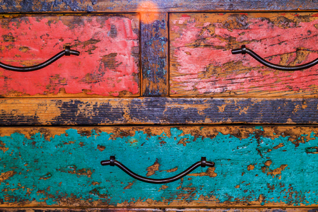 Close up of an antique chest of drawers with peeling paint.