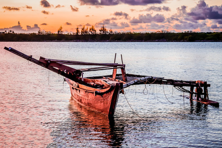 A wooden Micronesian canoe anchored in the bay at sunset.