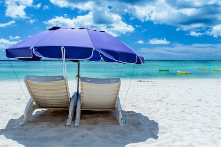 A pair of beach chairs under an umbrella on a deserted beach with white sand. Stock Photo - 64068046