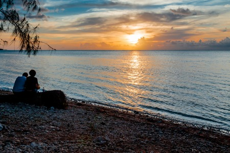 A couple in silhoutte sitting on a log under a tree enjoying the tropical sunset on the beach. Stock Photo - 64068047