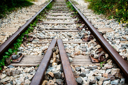 Rusty and pitted railroad tracks and guard rails.