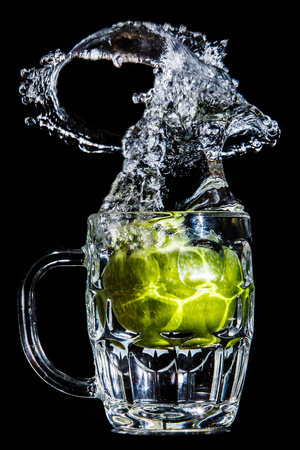 Artistic splash of a green apple created after being dropped into a clear goblet. Stock Photo - 76744455