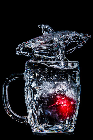 Artistic splash of a plum created after being dropped into a clear goblet. Stock Photo - 76385838