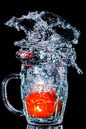Artistic splash of a tomato created after being dropped into a clear goblet. Stock Photo