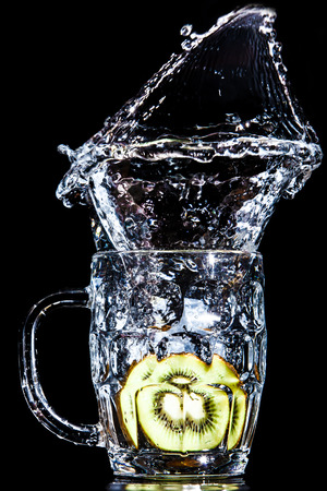 Artistic splash of a kiwi created after being dropped into a clear goblet. Stock Photo