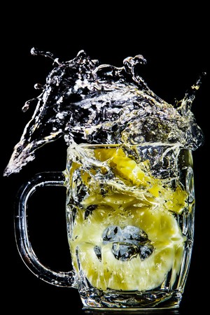 Artistic splash of pineapple rings created after being dropped into a clear goblet. Stock Photo