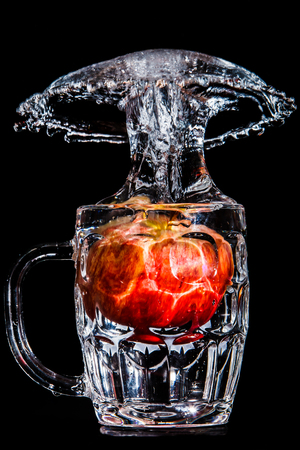 Artistic splash of a red apple created after being dropped into a clear goblet.