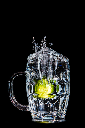 Artistic splash of a lime created after being dropped into a clear goblet.