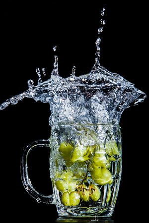 Artistic splash of a bunch of green grapes created after being dropped into a clear goblet.