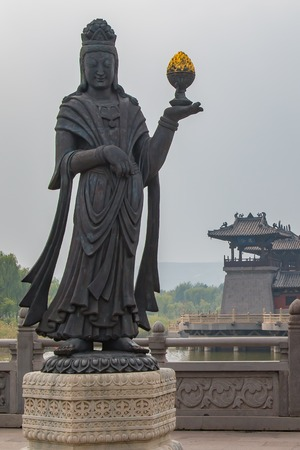 A large stone carved statue of a Buddhist Diety holding a golden object.