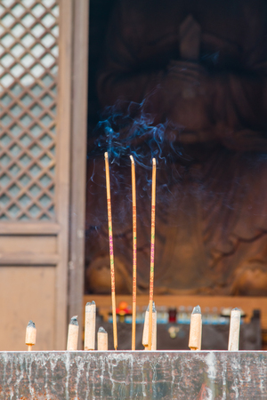 Burning incense at a stone alter in front of a temple housing a giant wooden sculpture of Buddha.
