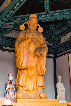 Buddhist diety, giant statue carved in wood and house in a temple.