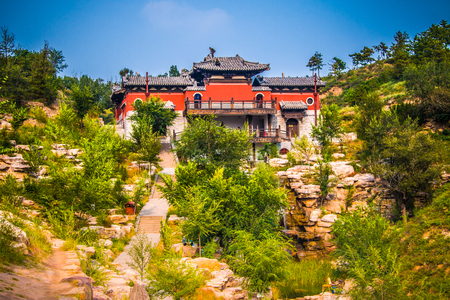 A buddhist monastery on top of a cliff under going renovations.