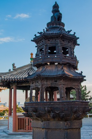 A pagoda shaped fire pit in a temples frount court yard blackened from years burning offerings during various ceremonies.