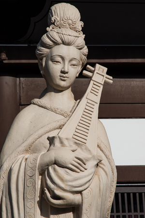 Clay statue of a maiden holding a chinese musical instrument.