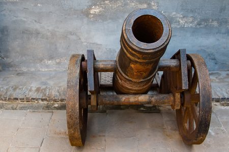 Close up of a small rusting cannon mounted on a rusting cart