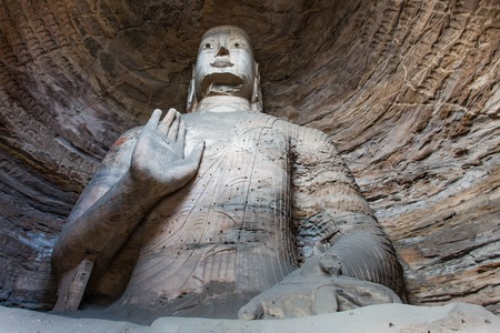 Giant Buddha carved from stone, housed in a cave at the Yungang Grottos Stock Photo