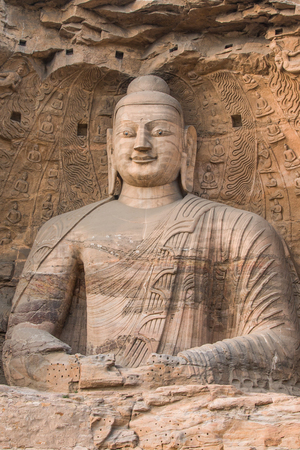 Giant Buddha carved from a reddish brown stone, housed in a cave at the Yungang Grottos