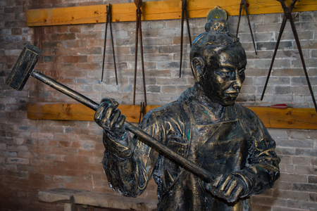 Close up of a metal statue of a blacksmith in his workshop.