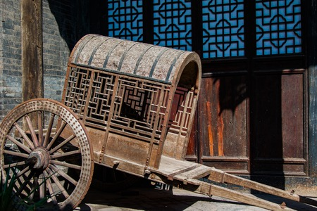 An ancient, antique covered, pull cart parked in front of a preserved centuries old building.