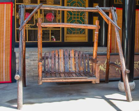 An antique twin seat swing made from chinese red pine.