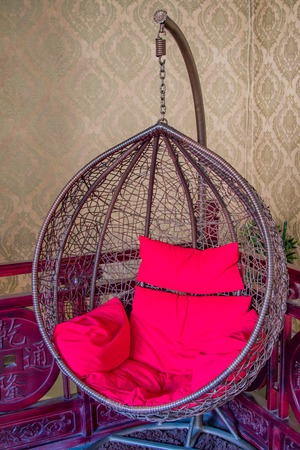 A hanging wicker basket type chair with red cushions against an antique red wood fence