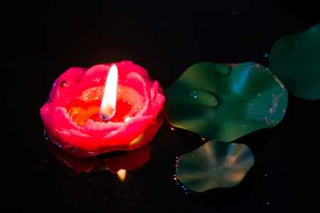 A floating red candle amonst some lily pads in a pond. Stock Photo