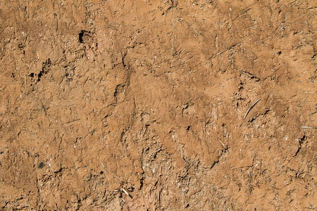 Close up of an earthen wall made of compacted mud and straw.