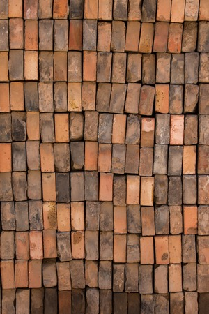 Close up of a wall made up of vertically stacked bricks