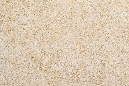 Close up of a beige cement block revealing a relatively find texture.