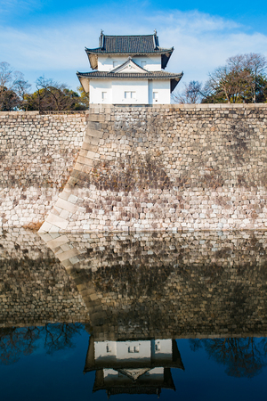 The Osaka Castle guard house at the edge of the complex wall, reflected on the moat