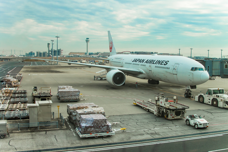 A docked Japan Airlines airplane about to be loaded and boarded.