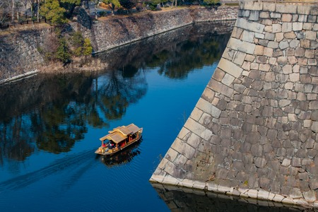 A tour boat sailing in the moat around Osaka Castle