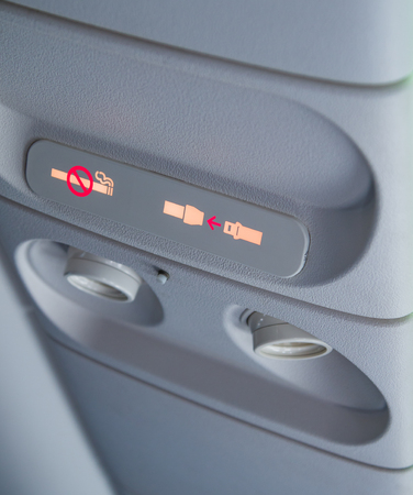 The no smoking, fasten seatbelt sign all lit up during a flight.
