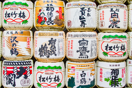 A wall of sake barrels used as decor outside a shrine in Japan Editorial