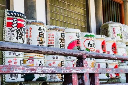 Traditional sake barrels stacked outside a shrine in Japan.