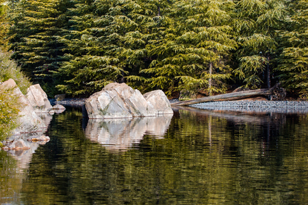 A boulder in a lake conceals the opening of a river.
