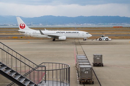 A Japan Airlines plane towed onto the tarmac ready for take off.