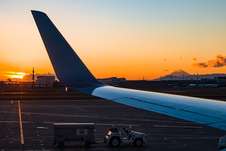 Looking out of an airplane window of a sunrise with Mount Fuji in the distance.