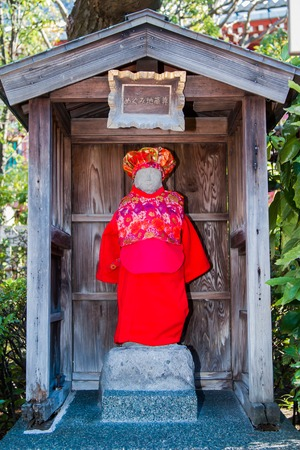 A shinto altar with a stone statue adorned with red clothes Editorial