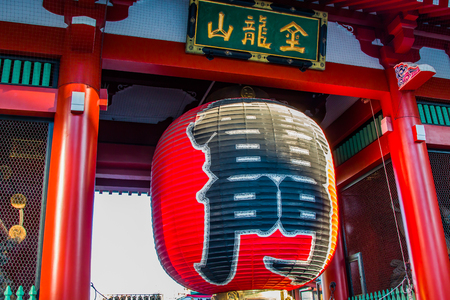 A giant red paper lantern, hanging over an entrance way to a temple. Stock Photo