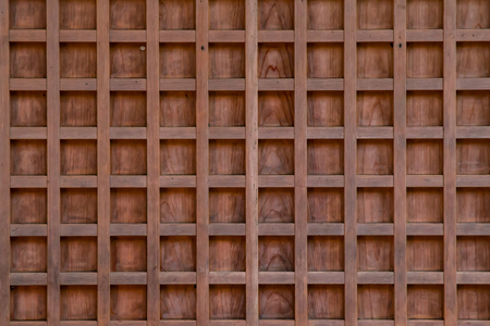 Close up of a light brown wood panel revealing its checkered pattern.