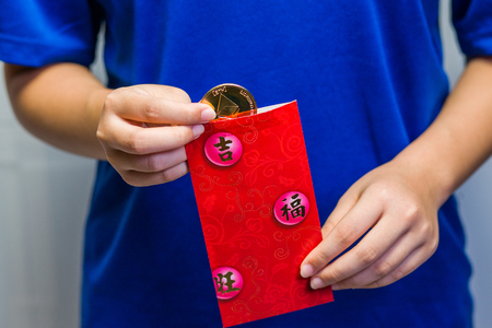 A close up of a girl removing an Etherium coin from a traditional red packet. Stock Photo