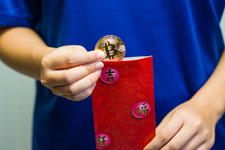 A close up of a girl removing a Bitcoin coin from a traditional red packet.
